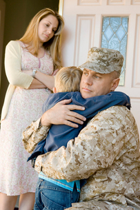 Military father embracing son (5-6) outside home  wife watの写真素材 [FYI03628271]