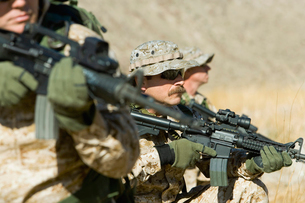 Soldiers aiming rifles in fieldの写真素材 [FYI03628292]