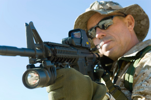 Soldier aiming rifle  outdoors  (close-up)の写真素材 [FYI03628293]
