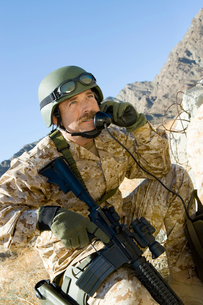 Soldier using field phone in mountainsの写真素材 [FYI03628299]