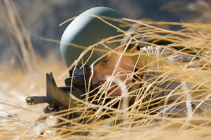 Soldier aiming rifle  hiding in long grass  (close-up)の写真素材 [FYI03628303]