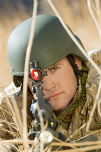 Soldier aiming rifle  hiding in long grass  (close-up)の写真素材 [FYI03628304]
