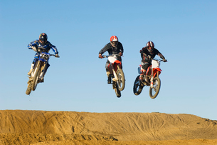Three motocross Racers in mid-airの写真素材 [FYI03628336]