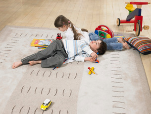 Brother and sister (3-6) laying on rug in homeの写真素材 [FYI03628381]