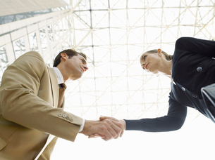 Businessman and businesswoman shaking hands  (low angle viの写真素材 [FYI03628398]