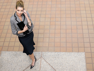 Businesswoman using mobile phone  indoors  (elevated view)の写真素材 [FYI03628409]