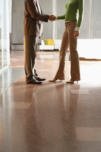 Businesspeople shaking hands  indoors  low sectionの写真素材 [FYI03628438]