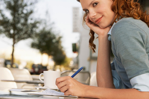 Young woman writing at outdoor cafe  close-upの写真素材 [FYI03628447]
