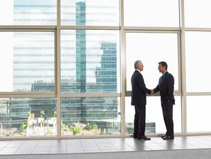 Businessmen shaking hands in office buildingの写真素材 [FYI03628454]