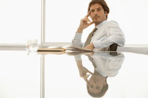 Serious businessman sitting at conference tableの写真素材 [FYI03628476]
