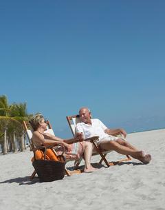 Senior couple on sunloungers on tropical beachの写真素材 [FYI03628525]