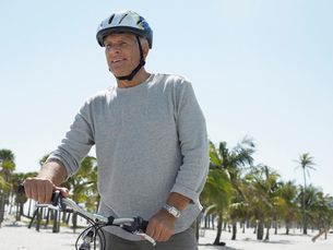 Senior man on bicycle on tropical beachの写真素材 [FYI03628529]
