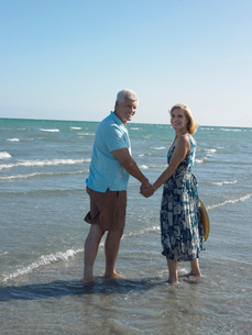 Senior couple walking on tropical beach  back viewの写真素材 [FYI03628536]