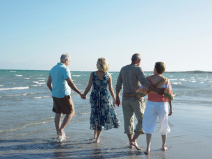 Two senior couples walking on beach  back viewの写真素材 [FYI03628543]