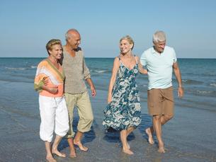Two senior couples walking barefoot on beachの写真素材 [FYI03628544]