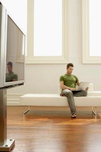 Man using laptop on sofa in modern apartmentの写真素材 [FYI03628545]
