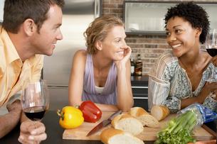Friends talking while preparing dinner  portraitの写真素材 [FYI03628569]