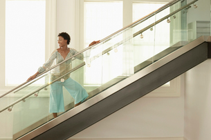 Young woman standing on modern glass stairs  portraitの写真素材 [FYI03628572]