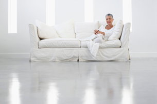 Woman sitting on sofa in empty white room  portraitの写真素材 [FYI03628590]