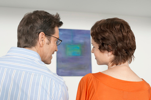 Couple discussing painting in art galleryの写真素材 [FYI03628602]
