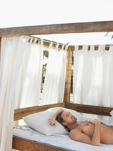 Man lying on four poster bed on beach  half lengthの写真素材 [FYI03628613]