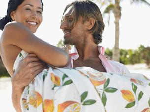 Man carrying woman on beach  half lengthの写真素材 [FYI03628615]
