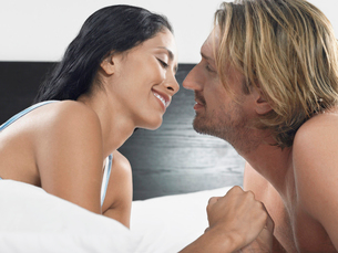 Couple about to kiss on bed  head and shouldersの写真素材 [FYI03628620]
