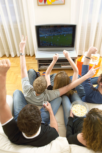 Friends watching TV and celebrating  view from aboveの写真素材 [FYI03628628]
