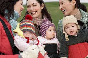 Three mothers with babies in slings chatting outdoorsの写真素材 [FYI03628633]