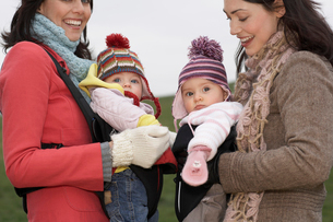 Two mothers in park with babies in slings standing face toの写真素材 [FYI03628634]