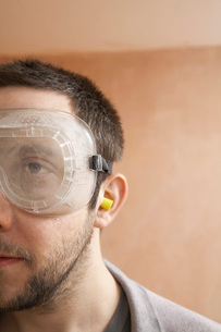 Man wearing protective eye goggles and earplugs indoor  clの写真素材 [FYI03628653]