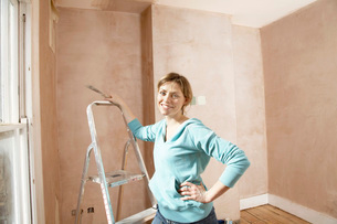 Woman standing by step ladder with scraping tool in handの写真素材 [FYI03628675]