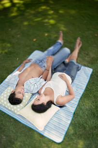 Couple lying down side by side on picnic blanket in parkの写真素材 [FYI03628704]