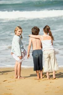 Three children standing at water edge on beach  back viewの写真素材 [FYI03628711]