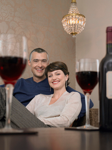 Smiling couple sitting at table in living room  wine glassの写真素材 [FYI03628738]