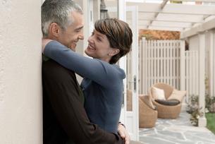 Smiling couple embracing on patioの写真素材 [FYI03628753]