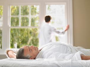 Man relaxing in bed  wife looking through window in backgrの写真素材 [FYI03628763]