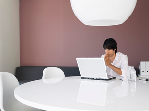 Asian businessman using white laptop in contemporary officの写真素材 [FYI03628764]