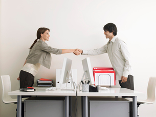 Man and Woman Shaking Hands over Desks  side viewの写真素材 [FYI03628779]