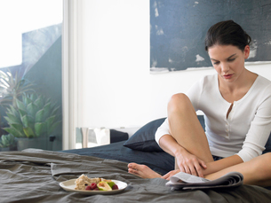 Woman sitting on bed with food  reading paperの写真素材 [FYI03628787]
