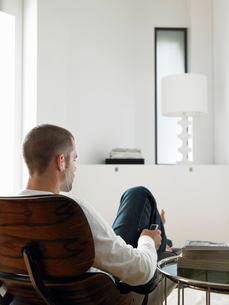 Man Sitting in Chair Listening to MP3 Player  back viewの写真素材 [FYI03628795]