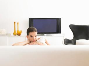 Woman sitting on sofa in modern living roomの写真素材 [FYI03628801]