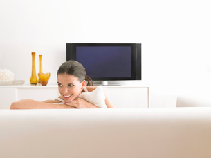 Woman sitting on sofa in modern living roomの写真素材 [FYI03628803]