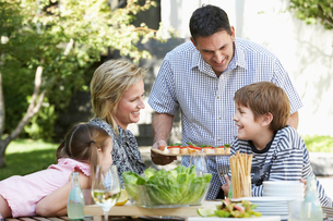 Family of four having lunch outdoors  portraitの写真素材 [FYI03628814]