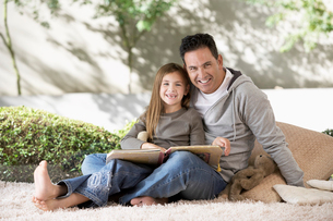 Father and daughter reading on floor  portraitの写真素材 [FYI03628823]