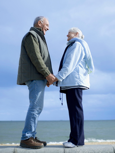 Senior couple standing on wall by water  holding handsの写真素材 [FYI03628846]