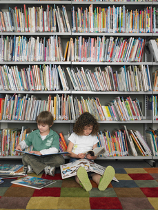 Boy and girl sitting on library floor reading booksの写真素材 [FYI03628880]