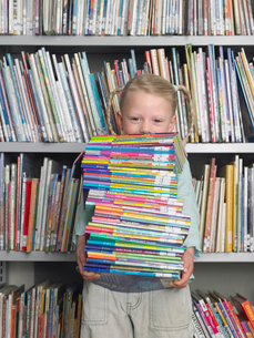 Girl holding stack of books in library  portraitの写真素材 [FYI03628882]