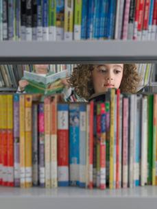 Girl selecting books from library bookshelfの写真素材 [FYI03628883]