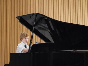 Pre teen boy playing piano in music classの写真素材 [FYI03628895]